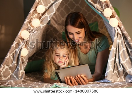Happy woman and her little daughter with tablet computer in hovel at home #1480007588
