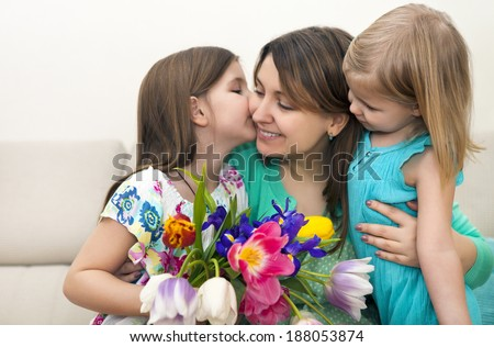 Happy woman and her little daughters in the living room Mother day concept