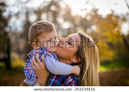 Happy woman and her little son. Mother kissing her toddler boy.
