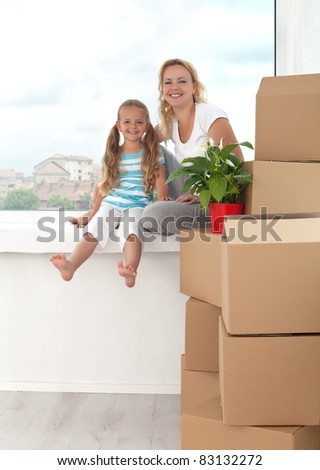 Happy woman and little girl in a new home sitting on windowsill with boxes and plant - moving theme