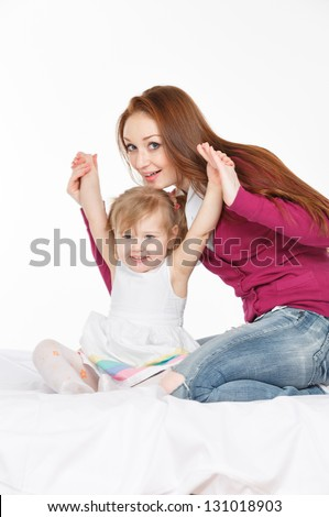 Happy woman and young girl (child) in bed smiling. Mother day concept.