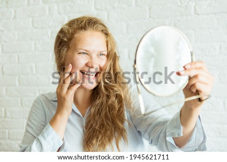 Happy woman applying cream and looking at mirror over grey background. Concept about body positivity, self esteem, and body acceptance Сток-фото ©