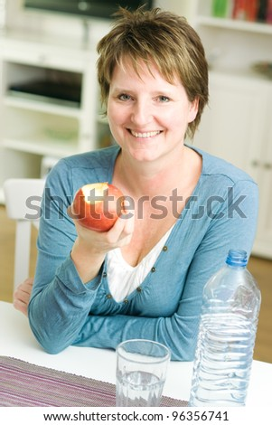 Happy woman at home holding apple and smiling at camera