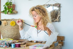 Happy woman at home work with beads and cords producing cheaper jewelry- modern female alternative job at home at the table - colorful trendy fashion young female