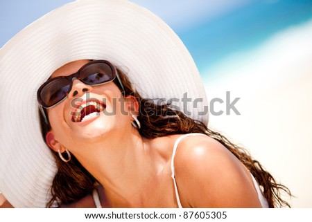 Happy woman at the beach wearing hat and sunglasses