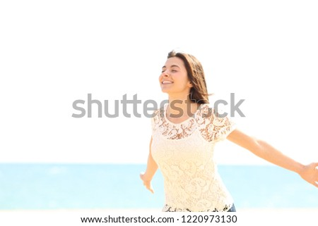 Happy woman breathing deep fresh air enjoying wind on the beach