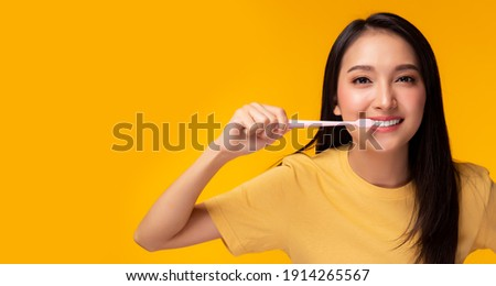 Happy woman brushing beauty tooth using toothbrush Young lady has beauty teeth Beautiful asian girl get strong tooth white teeth and nice tooth alignment Yellow background, copy space Dental care