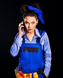 Happy woman builder calling mobile phone.