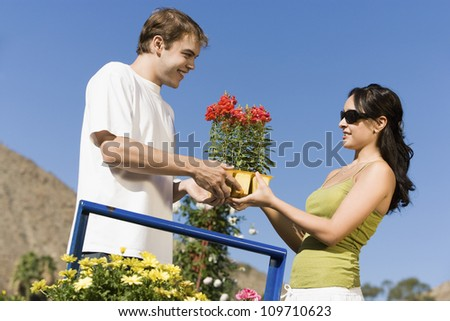 Happy woman buying potted plant from man at botanical garden