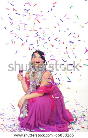 Happy woman celebrate new year party with champagne and looking up surprised at falling  confetti  over her while sitting down on floor