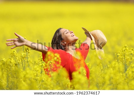 Happy woman celebrating vacation holding pamela stretching arms in a yellow field Сток-фото ©