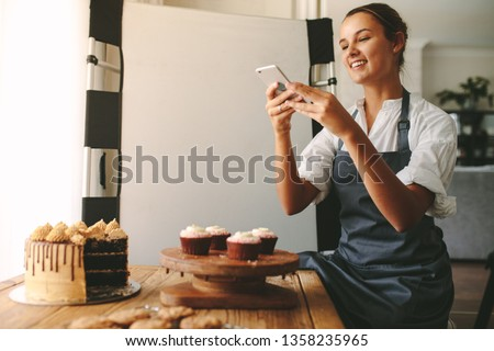 Happy woman chef taking a picture of pastries on a wooden board with smart phone while standing at the kitchen. Female baker taking pictures of the dessert for her food blog.
