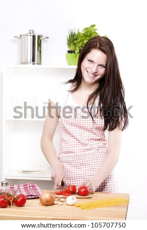 happy woman chopping tomato for spaghetti