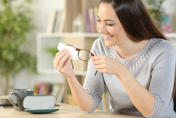 Happy woman cleaning eyeglasses with tissue paper sitting on a desk at home