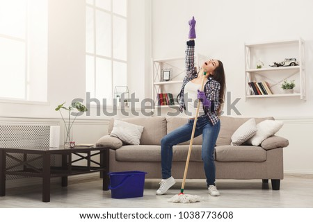 Happy woman cleaning home, dancing with mop and having fun, copy space. Housework, chores concept #1038773608