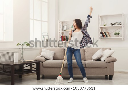 Happy woman cleaning home, singing at mop like at microphone and having fun, copy space. Housework, chores concept