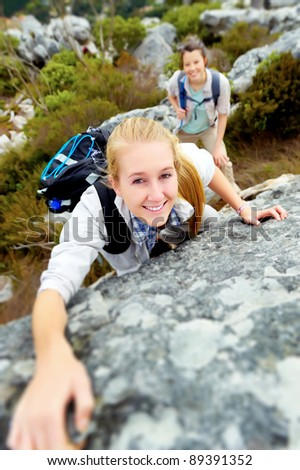 happy woman climbs a rock while trekking outdoors. carefree backpacker smiling at camera