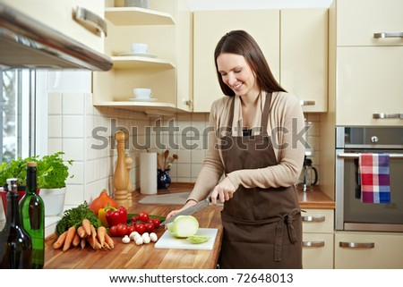 Happy woman cutting kohlrabi (Brassica oleracea var. gongylodes L.) in the kitchen