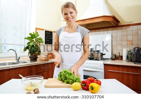 Happy woman cutting salad preparing healthy breakfast. Young female in white apron cooking meal for her family.