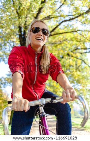 Happy woman cycling on bicycle, autumn park exercising. Young female cyclist commuting to work or relaxing in autumn nature.