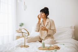 Happy woman doing routine skin care at home with beauty products. Woman sitting on bed at home and applying face cream.