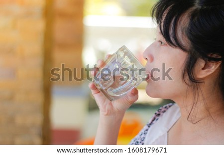 Happy woman drinking water while smiling.