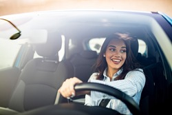 Happy woman driving a car and smiling. Cute young success happy brunette woman is driving a car. Portrait of happy female driver steering car with safety belt