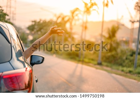 Happy woman Driving on Country Road into the Sunset
