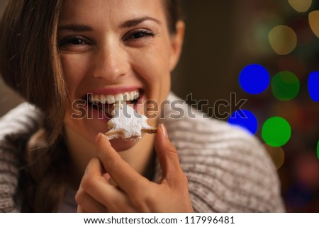 Happy woman eating Christmas cookie in front of Christmas lights