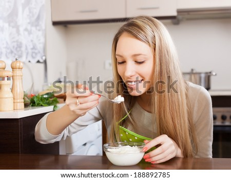 Happy woman eating cottage cheese at table