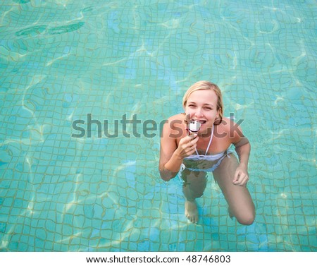 Happy woman eating ice cream on the pool