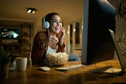 Happy woman eating popcorn and watching movie on desktop PC while enjoying at night at her apartment.