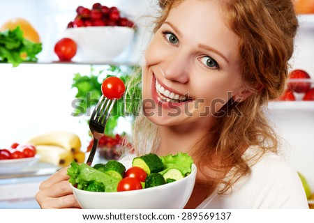 happy woman eats healthy food vegetable vegetarian salad about refrigerator