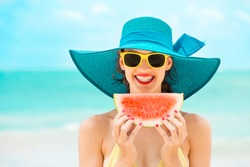 Happy woman enjoying a slice of watermelon on the beach.