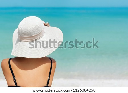 Happy woman enjoying beach relaxing joyful in summer by tropical blue water. Beautiful bikini model happy on travel wearing beach sun hat on beach. Girl on a tropical beach with hat