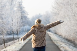 Happy woman enjoying fresh air during walk in winter nature. Fashion model wearing fur coat and knitted hat with arms outstretched outdoors. Cold weather with frozen trees