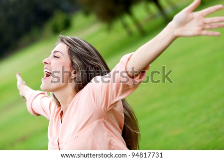 Happy woman enjoying her freedom outdoors with arms open