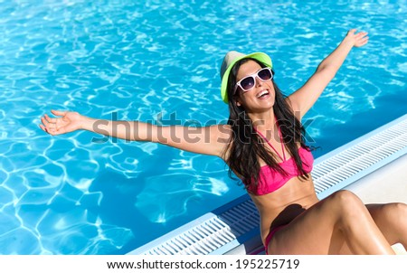 Happy woman enjoying summer vacation at swimming pool. Funky brunette girl on her summertime holidays.