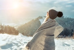 Happy woman enjoying sunset stay on mountain top of mountain and looking on beautiful winter snowy view. Christmas holiday. Snow day fun.