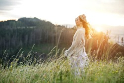 Happy woman enjoying sunset stay on the green grass on the forest peak of mountain. Travel, Summer, Holidays, Journey, Trip,.