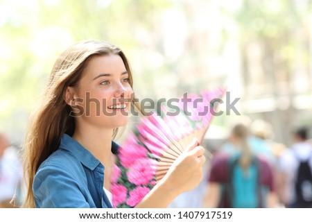 Happy woman fanning walking in the street on summer #1407917519