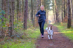 Happy woman full of vitality exercising her dog as they run together along a footpath through forest trees in a healthy active lifestyle concept