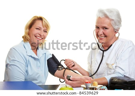 Happy woman getting blood pressure measure at health check