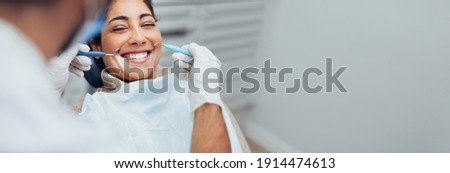 Happy woman getting dental checkup at dentistry. Dentist using dental equipment for examination of teeth of a female patient.