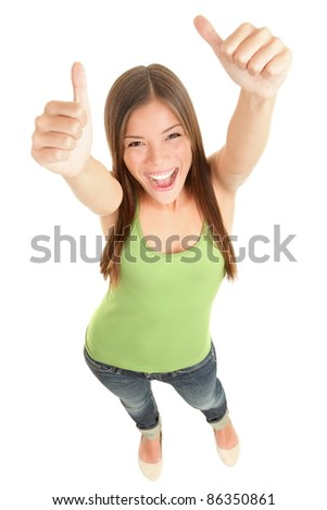 Happy woman giving thumbs up success hand sign standing excited and cheerful isolated in full length on white background. Young fresh and beautiful mixed race Caucasian Asian female model in her 20s.