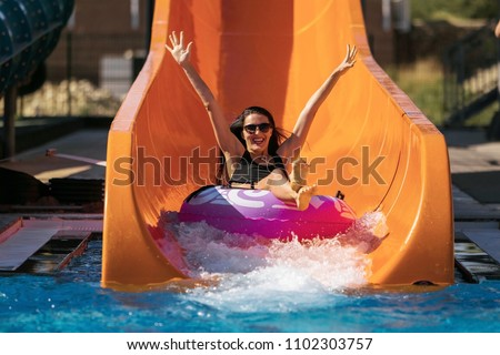happy woman going down on the rubber ring by the orange slide in the aqua park. Summer Vacation. Weekend on resort