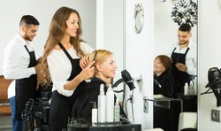 Happy woman hairdresser doing hairstyle for young men