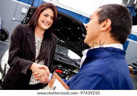 Happy woman handshaking with a mechanic after a good service