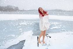 Happy woman hardening and winter swimming concept. Barefoot female enjoying cold snowy weather on an icy lake, mood-lifting and immune system boosting outdoor activities in the wintry landscape.