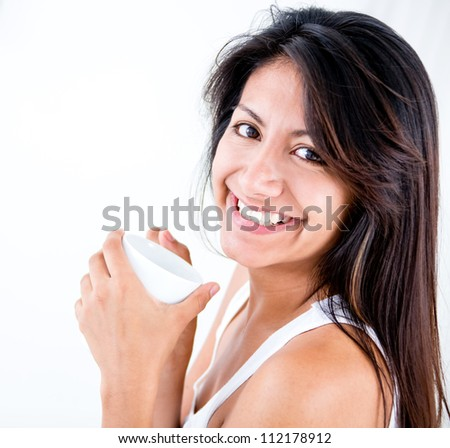 Happy woman having a hot drink and smiling